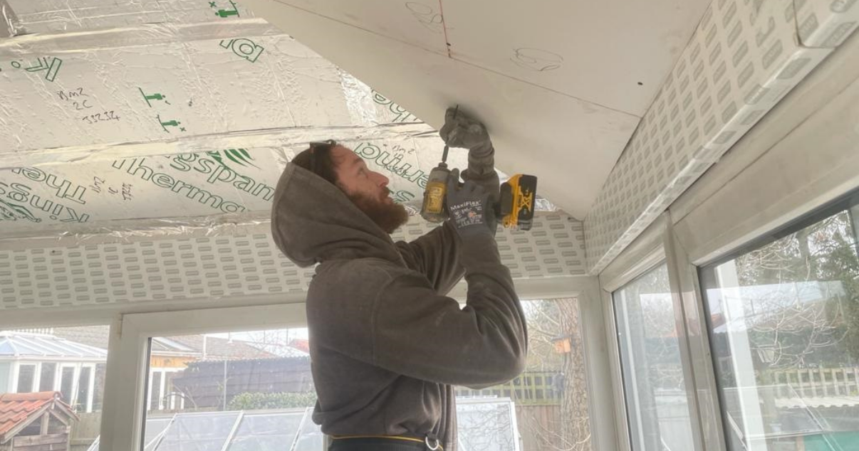 A man cutting the insulated plasterboard for a conservary roof conversion