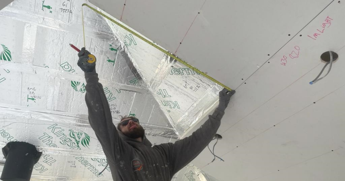 A man measuring the insulated plasterboard for a conservatory roof conversion