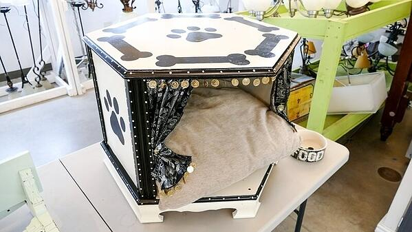"A hexagonal pet bed/pet ""cave"" with a pillow, curtains, and small medallions hanging off the opening. It's white with painted paw prints and bones."