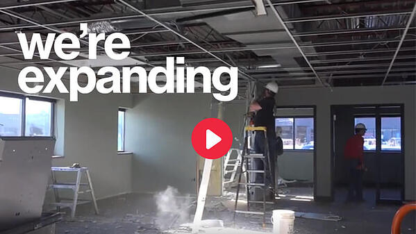"White text saying ""we're expanding."" The background is a photo of volunteers doing construction work inside of the New Brighton Store. A red ""play"" button is in the middle of the image."