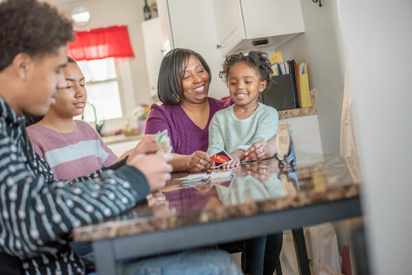 LaShonda and her family sitting at the kitchen table playing Uno.