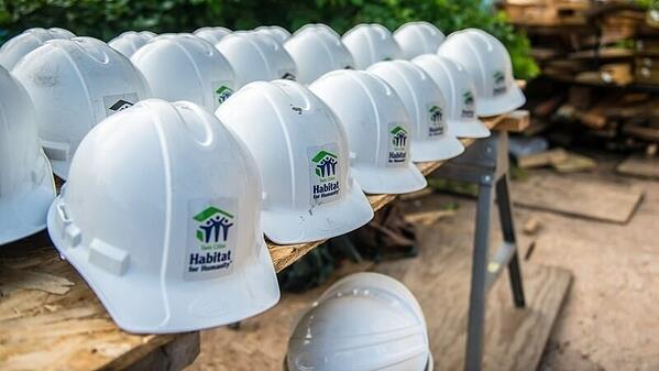 Three rows of white Twin Cities Habitat hard hats on a workbench.