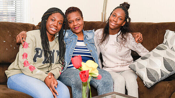 A Habitat homeowner with her two daughters on their couch.