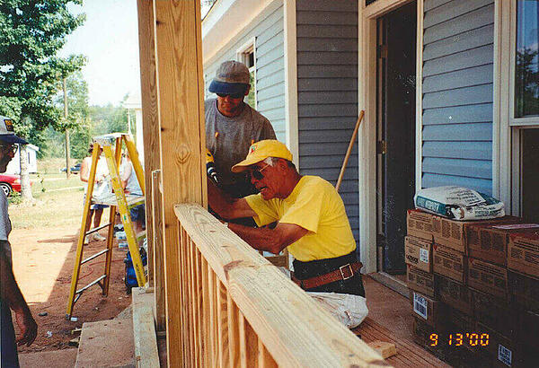 Kenny working on a porch with other volunteers, photo dated 9/13/2000.