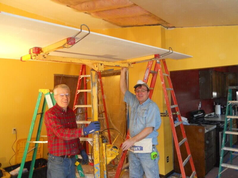 A photo of Jerry & Phil volunteering inside a home.