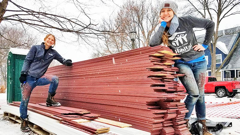 Two members of the homebuilding team posing with a pile of lumber.