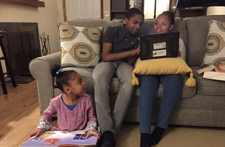 Angel's son Don helping his sisters with homework in their living room.