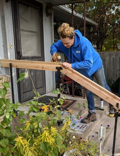 Ashley installing a railing on the front steps of a home.
