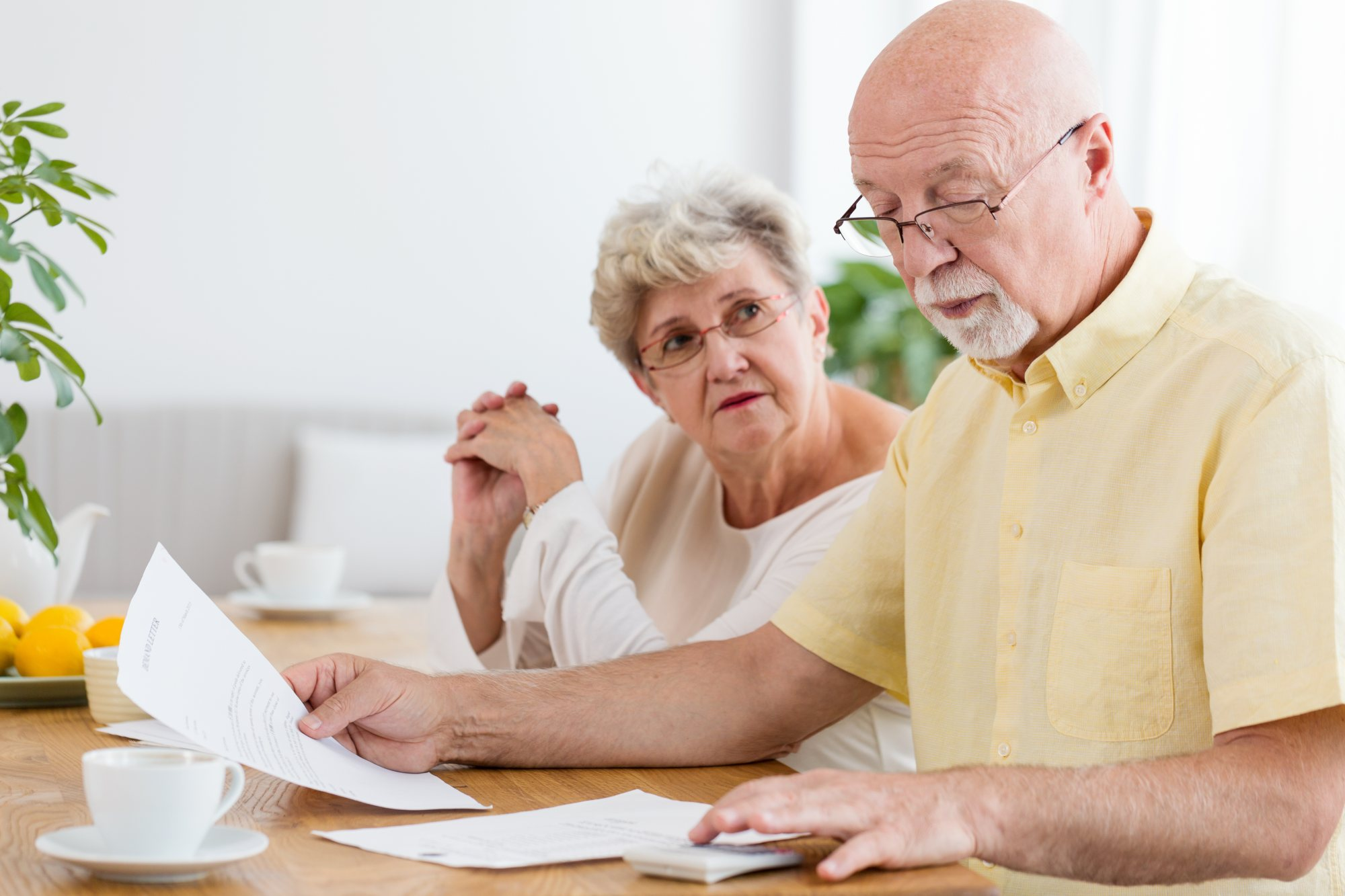 How Much Does it Cost to Age in Place_ - elderly couple, paperwork, cost, calculator