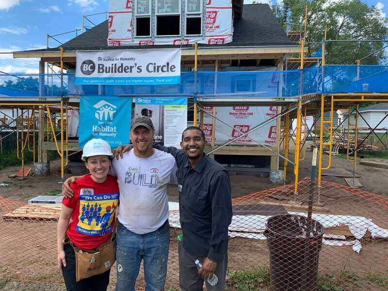 Corey, Catina, and Abdi standing outside a partially-finished home with the Builder's Circle and TC Habitat signs behind them.