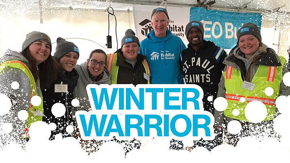 """Blue text reads """"Winter Warrior"""" with an abstract snow border at the bottom. The photo behind the text is of AmeriCorps members and volunteers wearing Winter Warriors hats and posing with Chris Coleman at the CEO Build."""