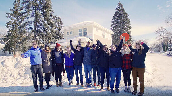 Volunteers celebrating outside a home build site in the snow.
