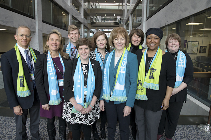 Advocates from Twin Cities Habitat for Humanity and other MN Habitat affiliates met with MN Senator Tina Smith (fourth from right) at Habitat on the Hill D.C. in 2019. They are standing in an office building atrium and are all wearing light blue and green Habitat scarves.