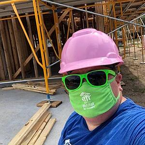A volunteer in front of a framed house, wearing a green mask and sunglasses, and a pink hard hat.