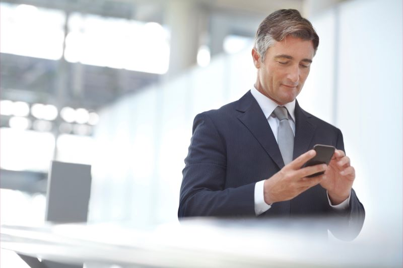 businessman using a cell phone in a commercial building-min