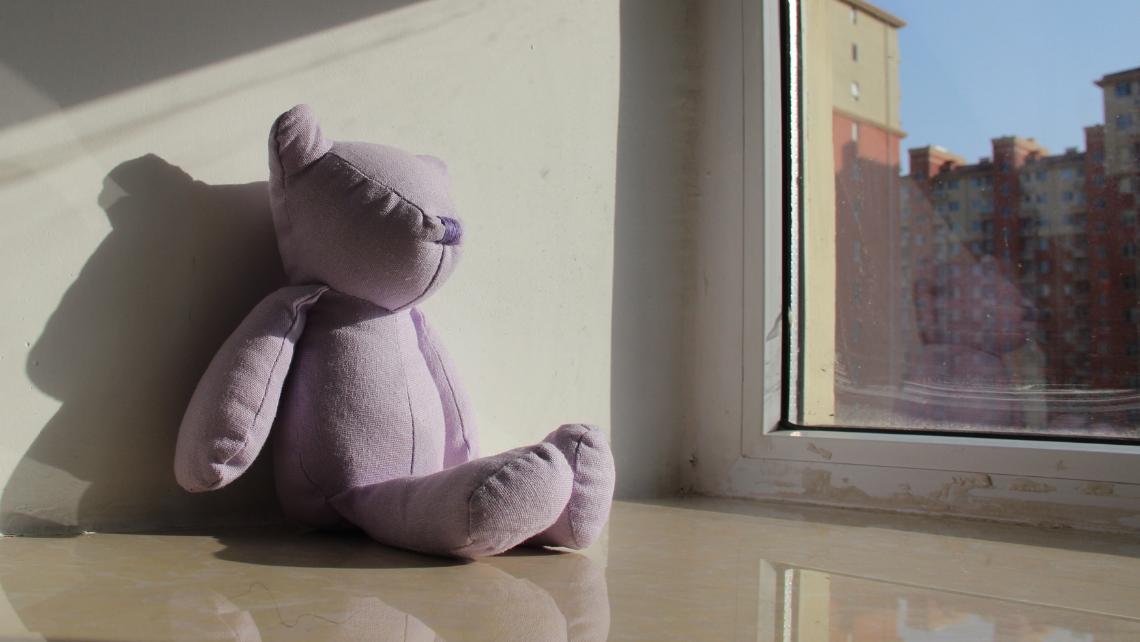 Korona-nalle istuu ikkunalla