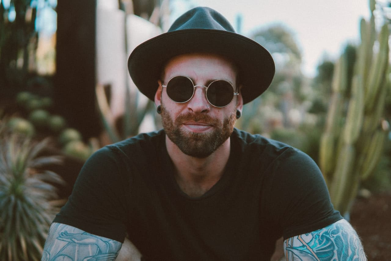 Tattooed man in hat and glasses