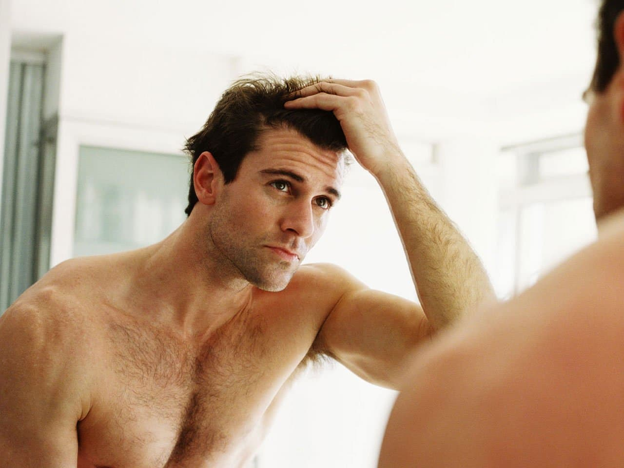 Man inspecting hairline in mirror