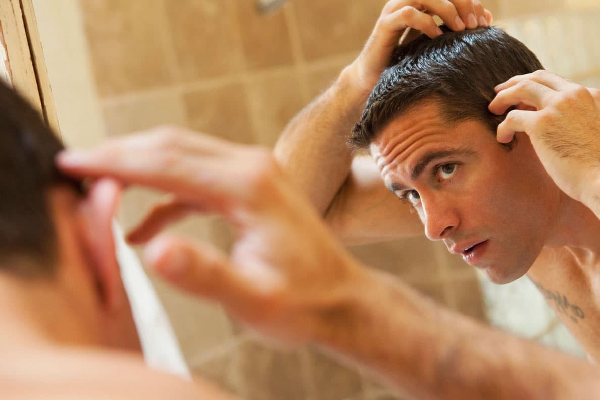 Man looking at hairline in mirror