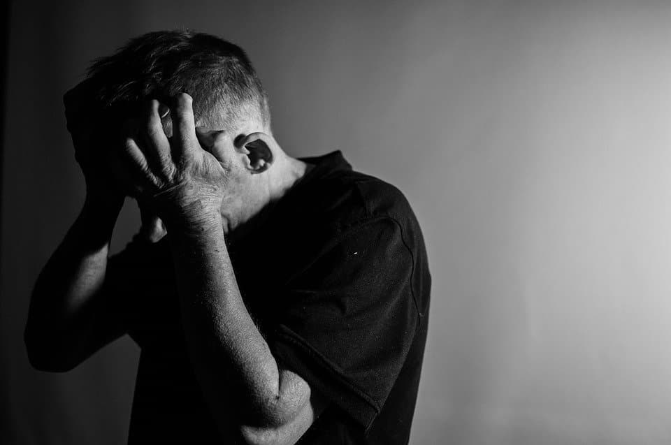 Distraught man holding head in hands