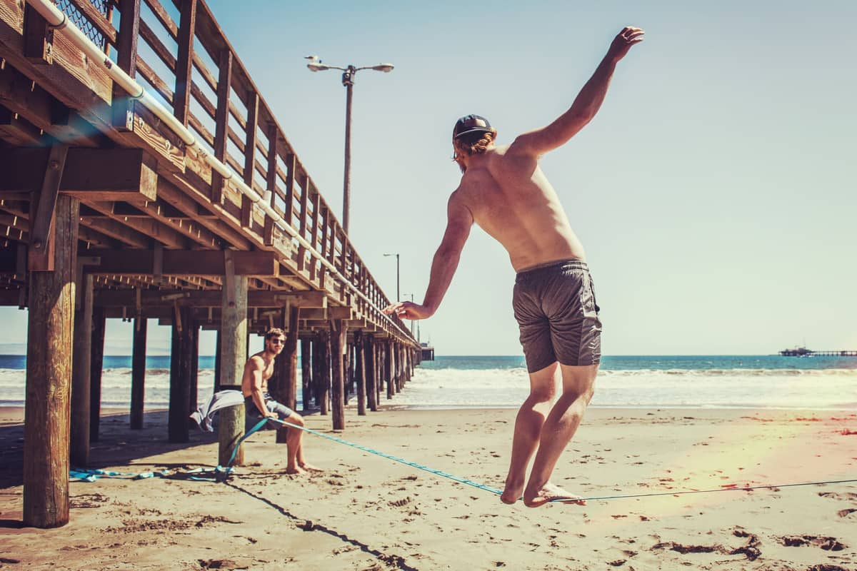 Man slacklining on beach