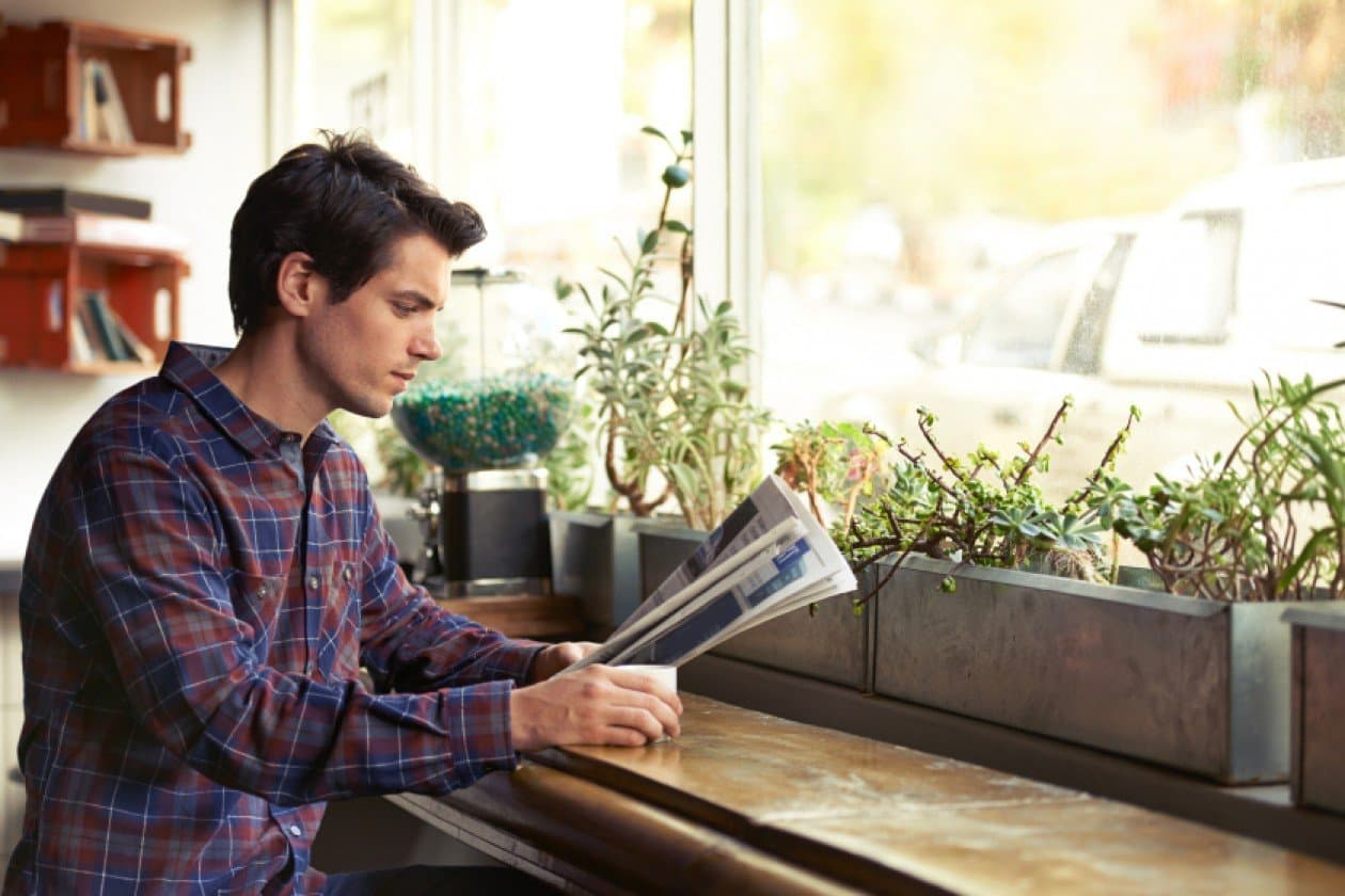 Man reading newspaper by the window