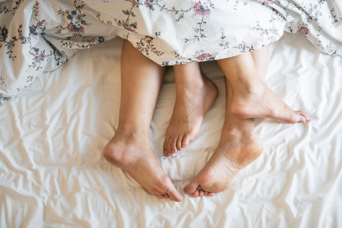 Feet of couple at bottom of bed