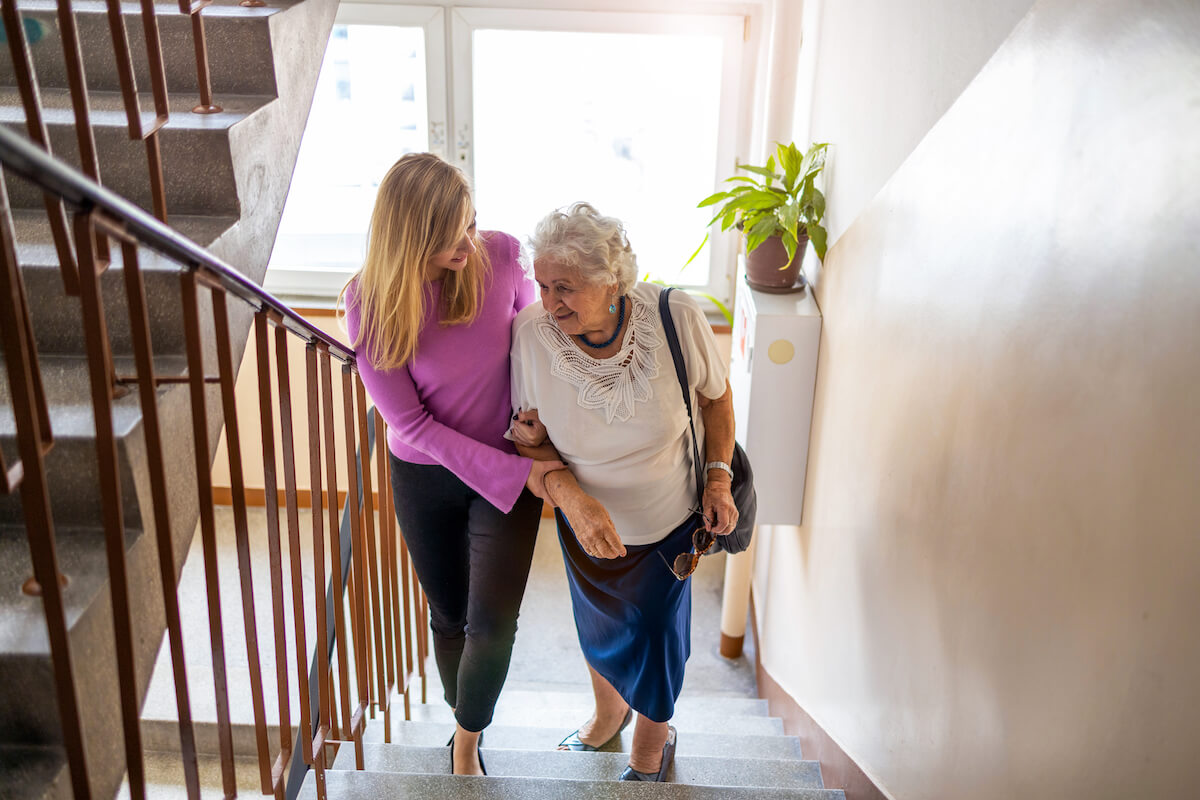 woman helping older woman up the stairs_home safety tips for seniors