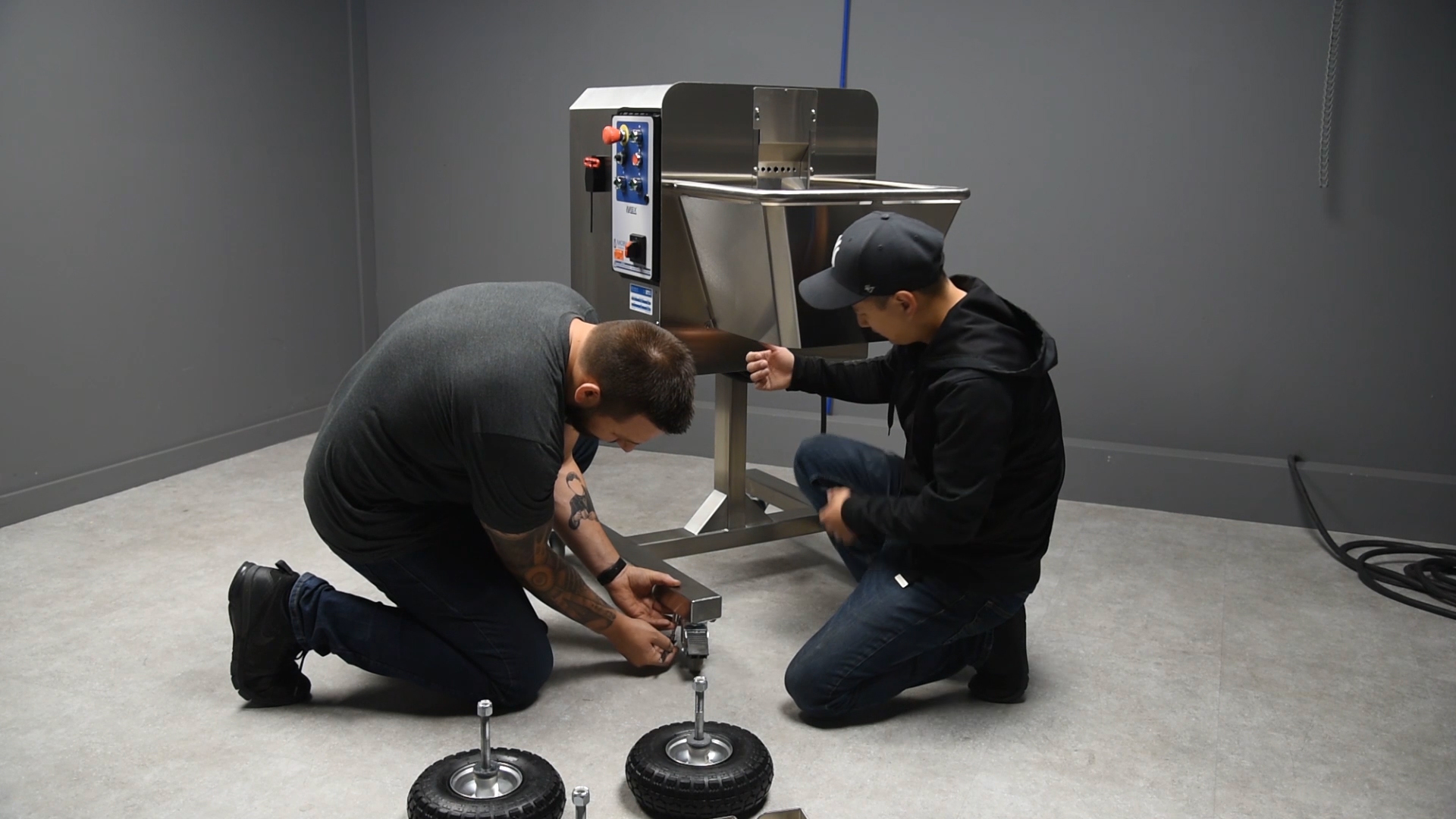 two men changing a wheel on a Mobius Bucker