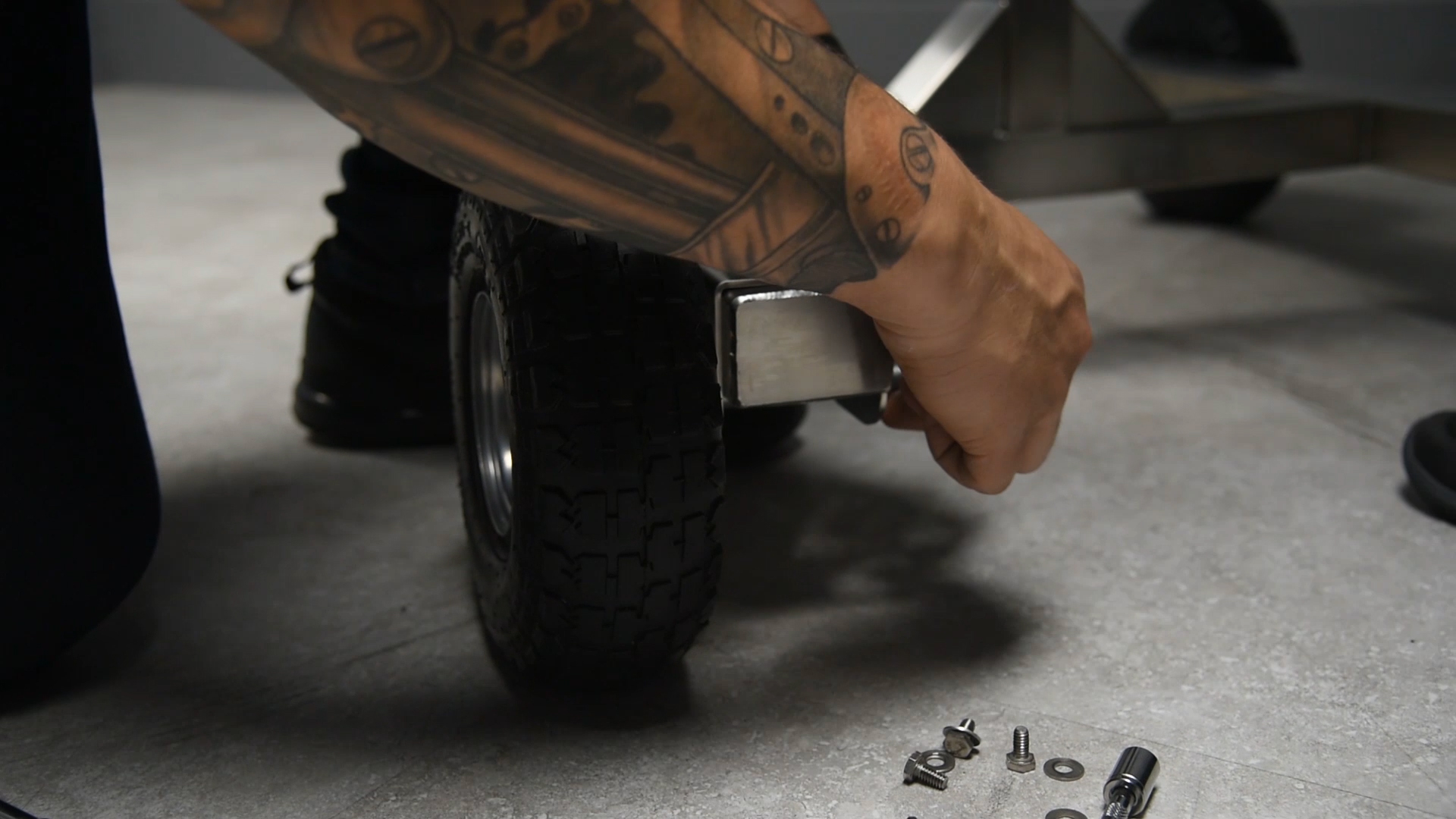 upslose image of man's hand putting wheel back on a Mobius Bucker