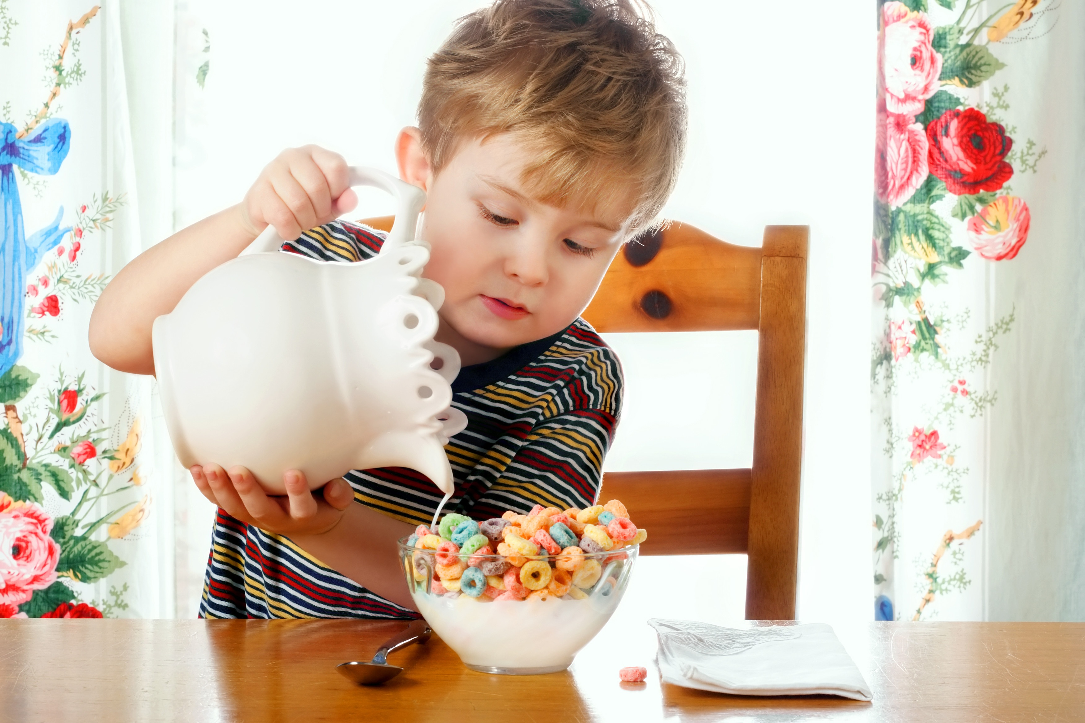 Boy pouring cereal into milk