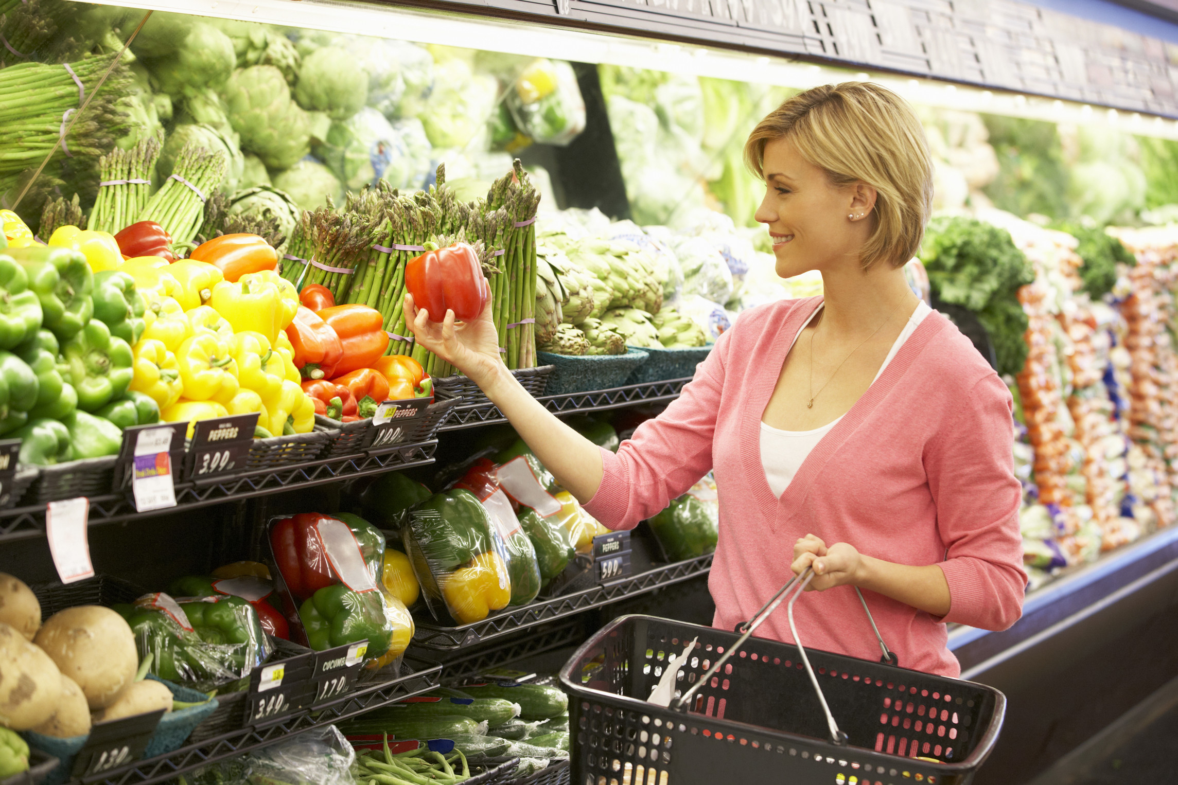 Woman grocery shopping looking colors of food