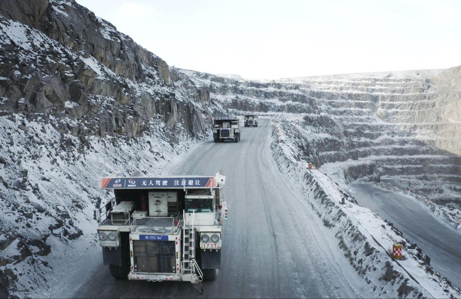 Mining trucks driving on road in open pit mine