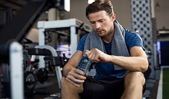 man with water bottle at gym drinking water to ensure proper healthy hydration