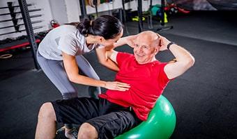 senior man with trainer doing rehab using pilates exercies