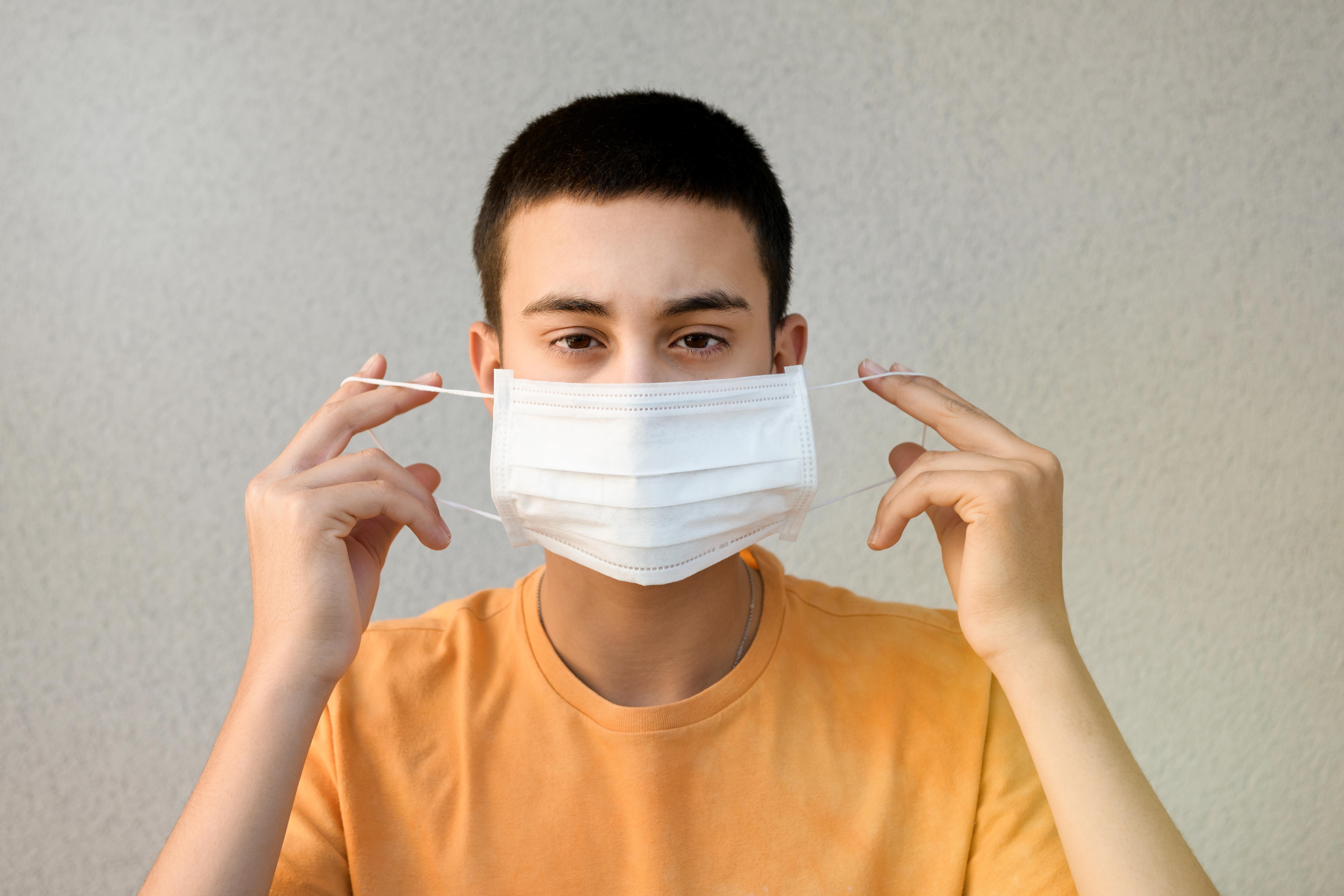 teenage-boy-holding-up-a-face-mask-GL762YQ