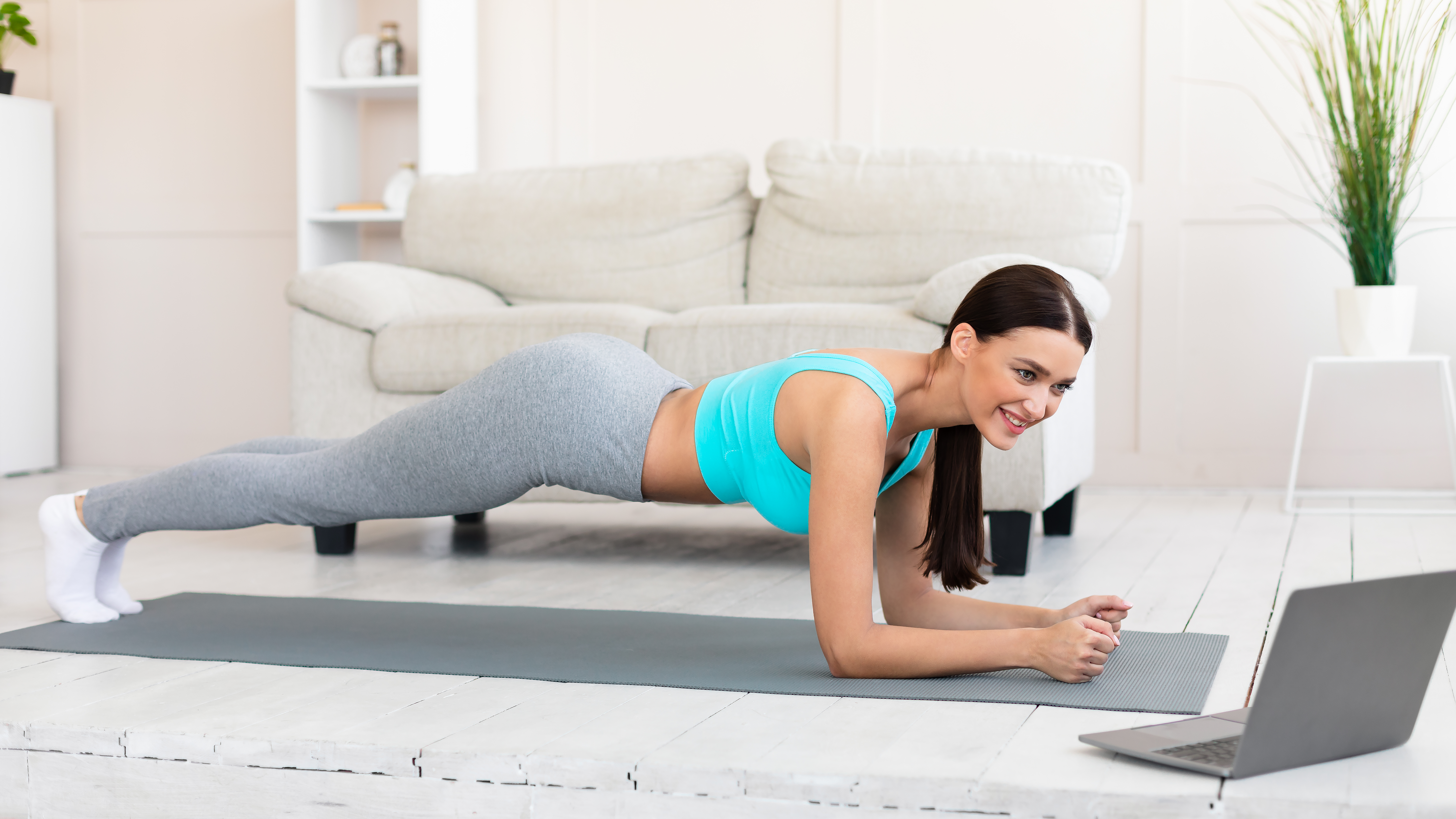 young-woman-at-laptop-exercising-doing-plank-durin-QKAWFD8