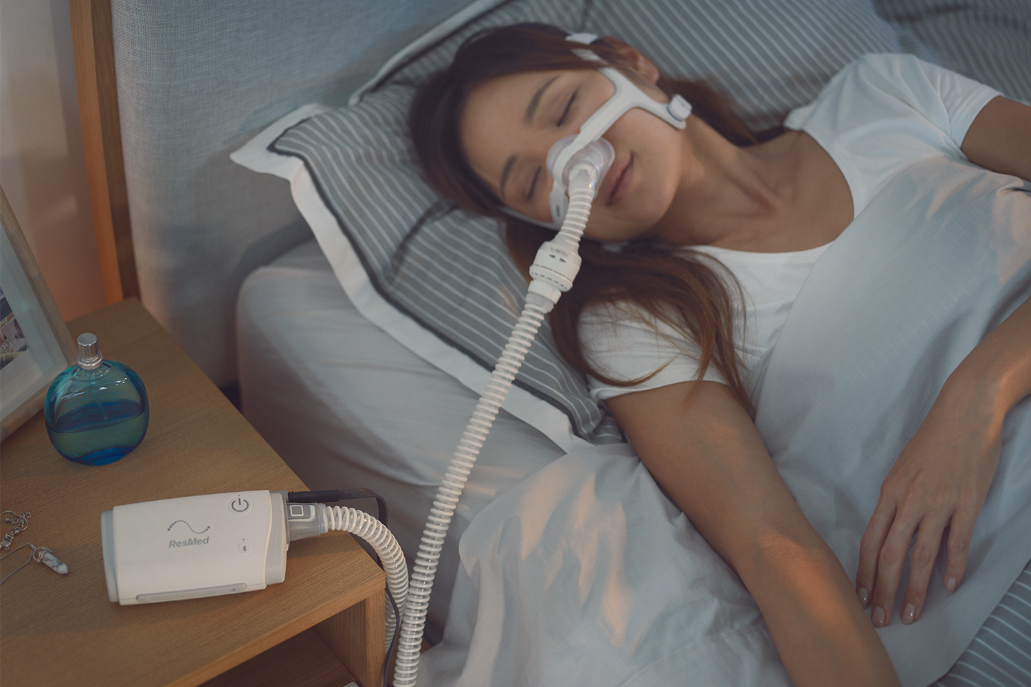 Woman Using AirMini Autoset CPAP Machine in Bed