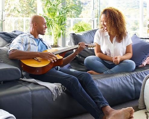 Man sitting on couch with guitar smiling at woman