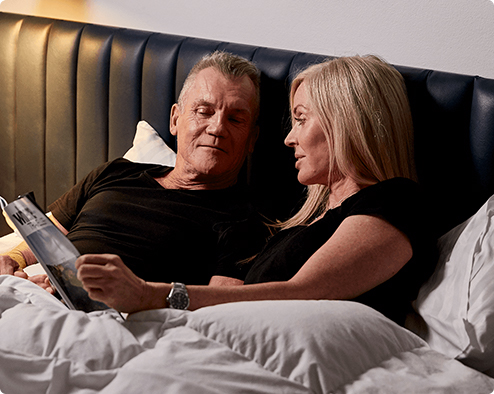 mature couple lying in bed reading magazine