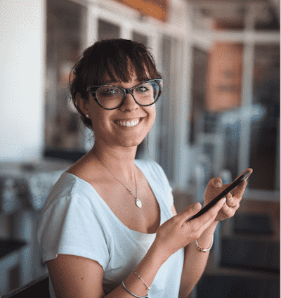 Woman smiling and holding her cell phone