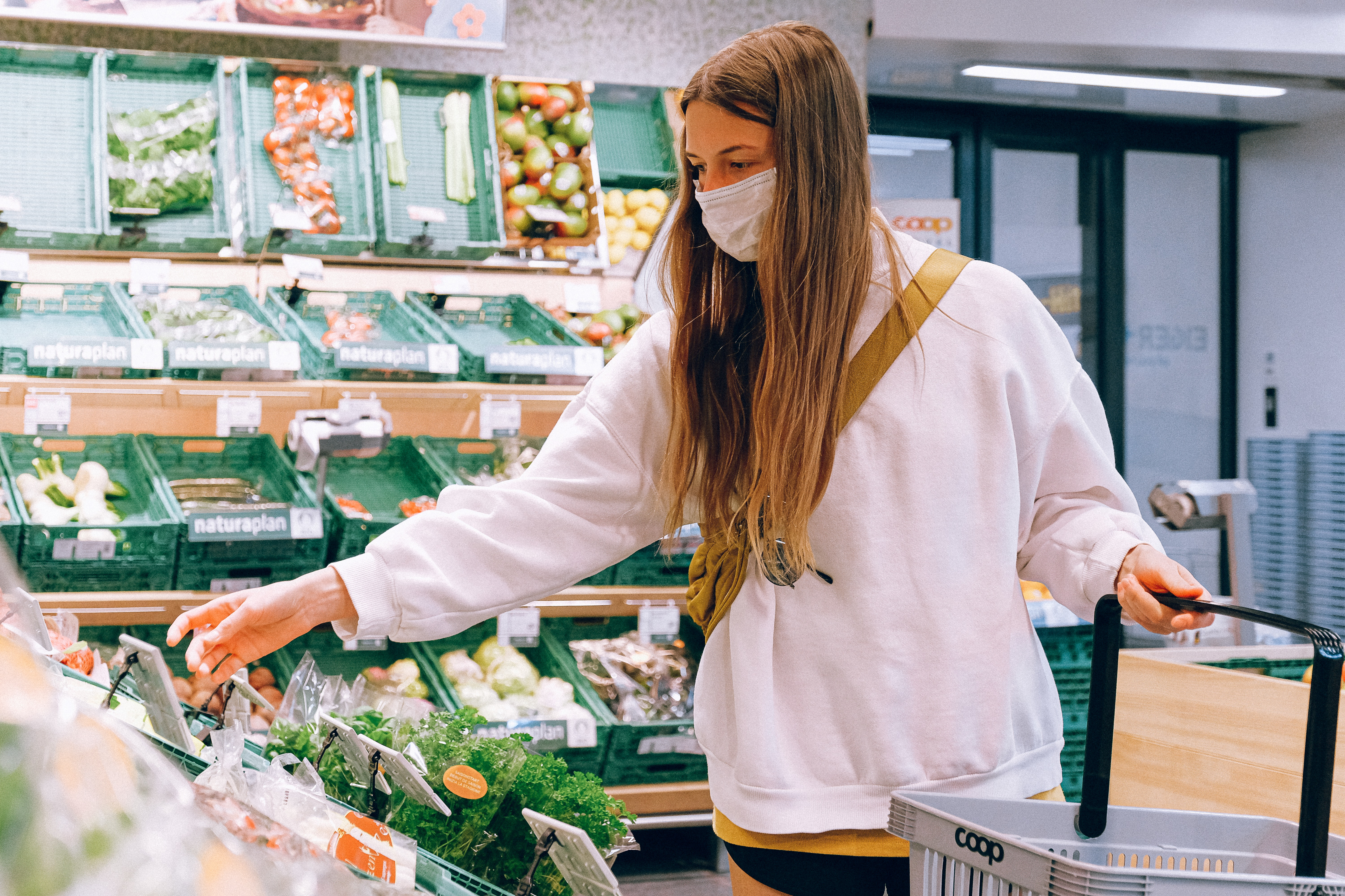 a masked woman shopping for vegetables